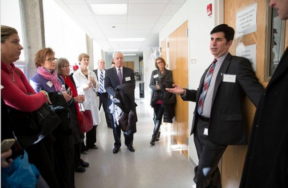 Dr. Borgia leading a team of SAA staff, swimmers and committee members on a tour of the SAA Laboratory for Cancer Research